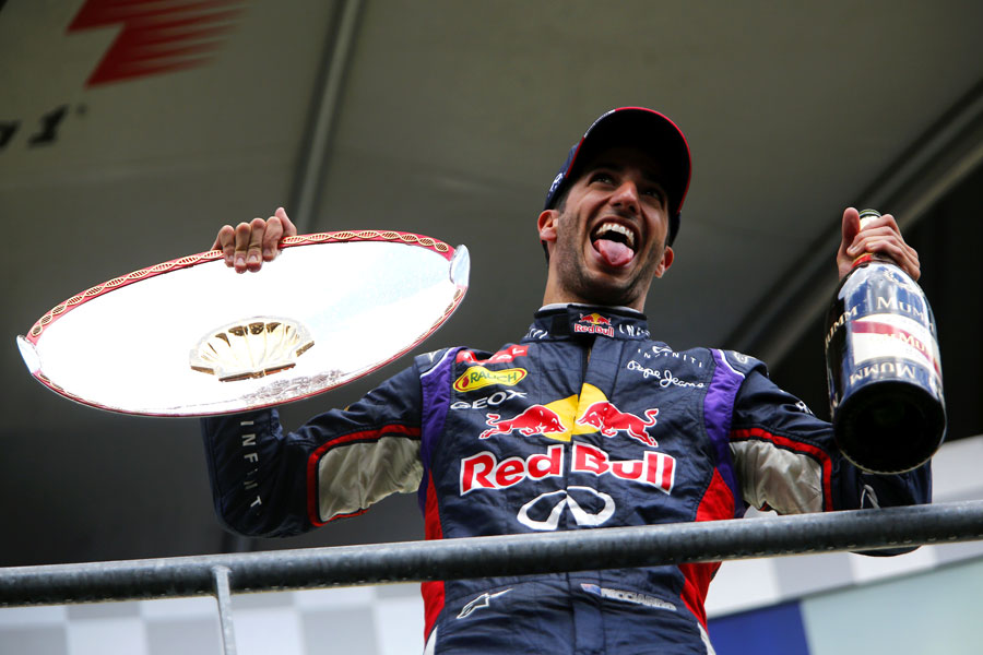 Daniel Ricciardo celebrates with the winner's trophy and champagne on the podium