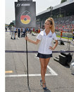 A grid girl waits by Nico Rosberg's grid slot before the race