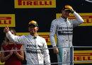 Nico Rosberg looks on as Lewis Hamilton takes to the podium