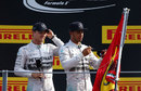 Nico Rosberg looks on as Lewis Hamilton signs a flag hoisted by fans beneath the podium