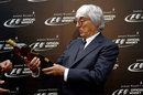 Bernie Ecclestone is presented with a bottle of whisky at a sponsor event