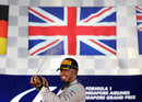 Lewis Hamilton sprays champagne on the podium underneath the Union Jack