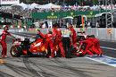 Kimi Raikkonen's Ferrari is wheeled back into the garage