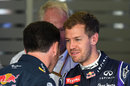 Christian Horner and Sebastian Vettel share a smile in the garage