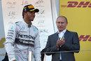 Russian president Vladimir Putin applauds race-winner Lewis Hamilton on the podium