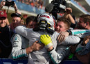 Lewis Hamilton celebrates with his mechanics in parc ferme