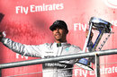 Lewis Hamilton celebrates with the winner's trophy on the podium