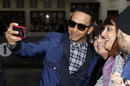 Lewis Hamilton poses for a selfie with fans outside BBC headquarters