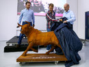 Sebastian Vettel unveils a bull statue on his farewell visit to Red Bull's factory with Christian Horner and Adrian Newey watching on