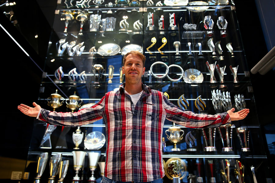 Sebastian Vettel poses in front of Red Bull's trophy cabinet during a farewell visit to the team's Milton Keynes factory