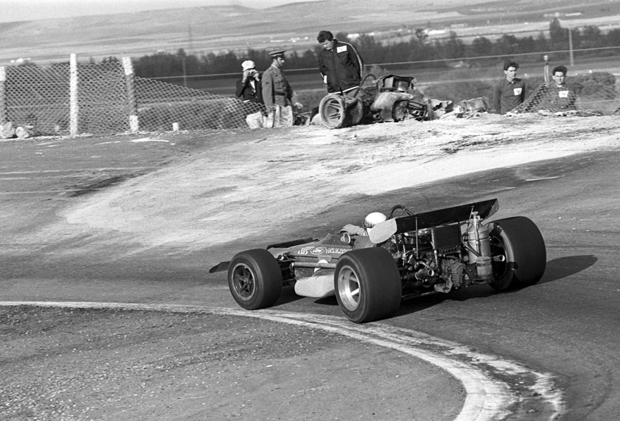 Jackie Stewart passes the burnt out wreck of Jackie Olivers's BRM