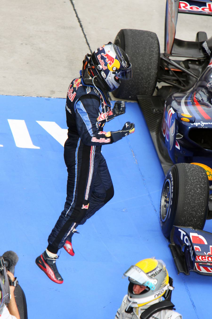 Sebastian Vettel jumps from his car, celebrating his first win of 2010