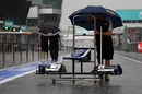A Williams nose cone is wheeled down a flooded Sepang pit lane