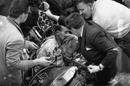 Stirling Moss is tended by medics after his crash at Goodwood