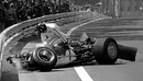 Graham Hill climbs from the wreckage of his Lotus