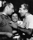 Stirling Moss is congratulated by Juan Manuel Fangio on winning the Italian Grand Prix