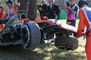 Kevin Magnussen's wrecked McLaren is picked up by marshals after his FP2 crash