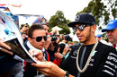 Lewis Hamilton signs autographs for fans on his arrival at the track