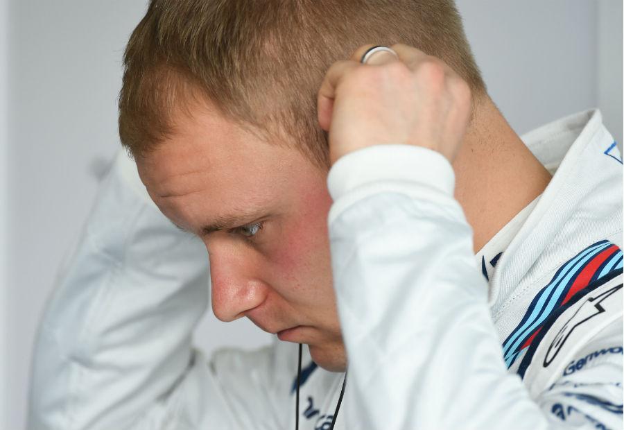 Valtteri Bottas adjusts his headphones in the garage