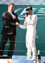 Lewis Hamilton shakes hands with film star Arnold Schwarzenegger on the podium