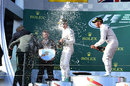 Race-winner Lewis Hamilton sprays Sir Jackie Stewart from the top step of the podium