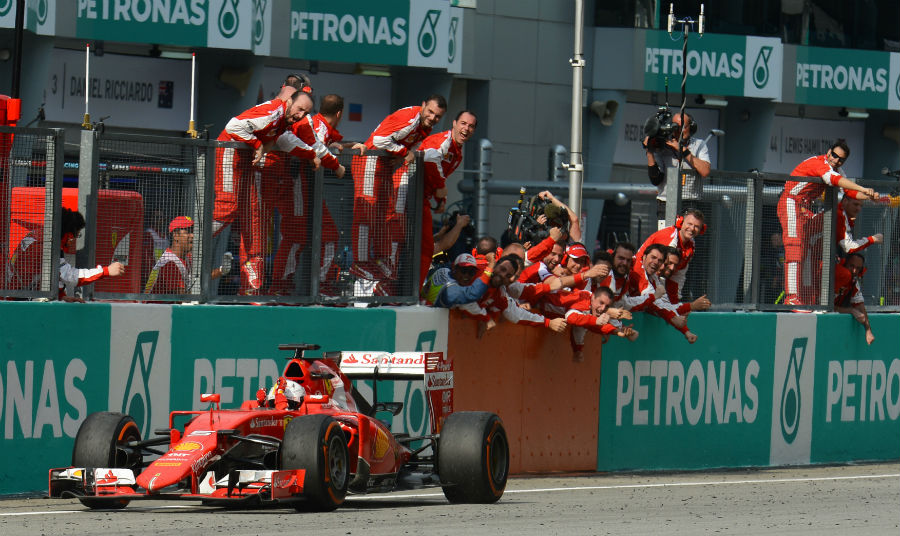 Sebastian Vettel and Ferrari celebrates as the German takes the chequered flag