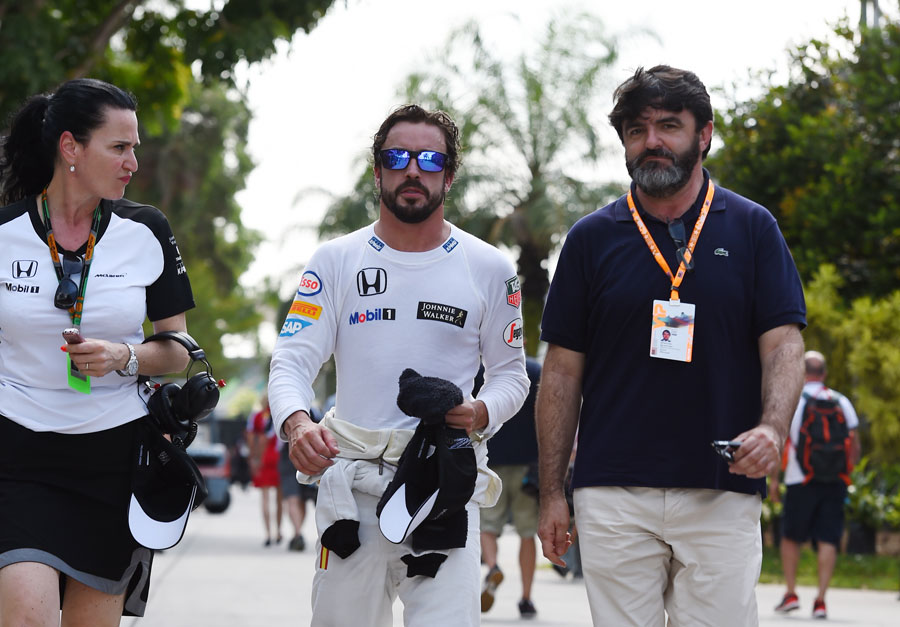 Fernando Alonso walks through the paddock after retiring from his first race with McLaren-Honda