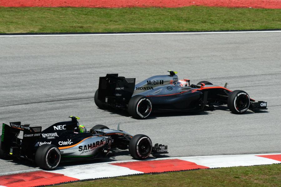 Jenson Button leads Force India's Sergio Perez through a corner