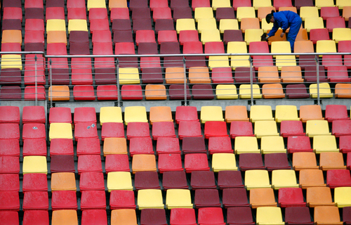 A worker cleans seats ahead of the Chinese Grand Prix