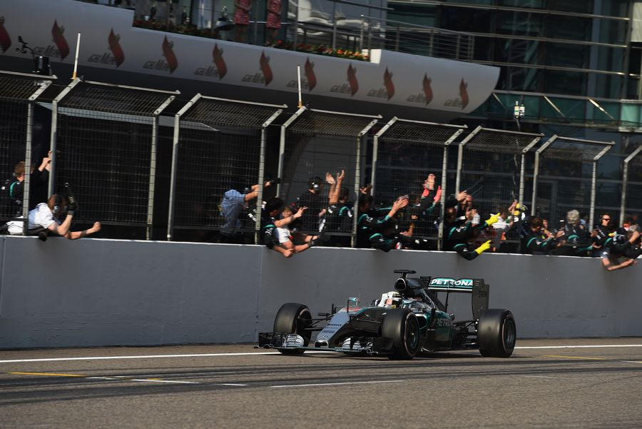 Race-winner Lewis Hamilton crosses the line