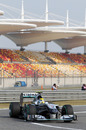 Nico Rosberg flashes past empty grandstands