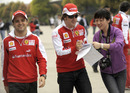 Felipe Massa walks on as Fernando Alonso signs for a fan