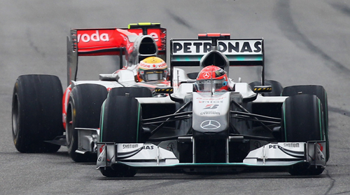 Michael Schumacher fights to hold off Lewis Hamilton