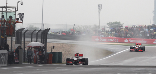 jenson Button takes the chequered flag from Lewis Hamilton