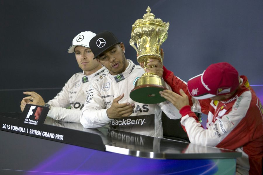 Sebastian Vettel takes a look at Lewis Hamilton's trophy during the press conference