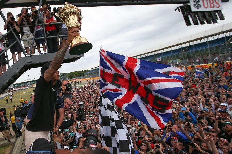 Race winner Lewis Hamilton celebrates with fans