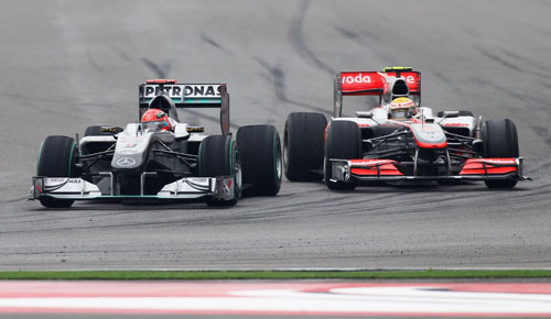 Michael Schumacher comes under pressure from Lewis Hamilton