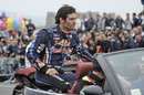 Mark Webber sits on the back of a car as he gets ready to take part in the Red Bull F1 Show Run