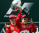 Michael Schumacher encourages Rubens Barrichello to take the winner's trophy