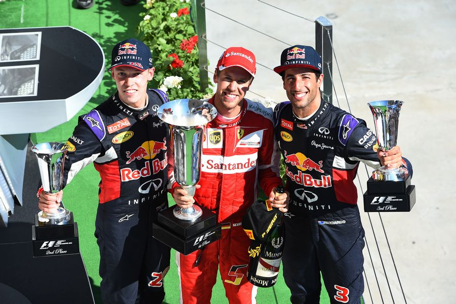 Top 3 pose with the trophies on the podium