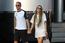 Jenson Button walks through the paddock with his wife Jessica