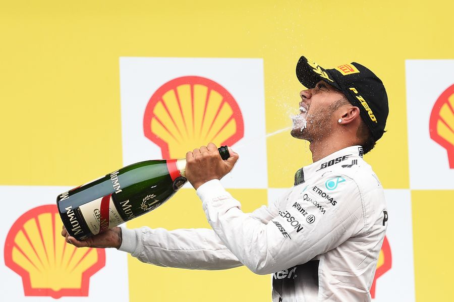 Lewis Hamilton celebrates his win on the podium with the champagne