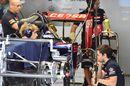 Toro Rosso mechanics work on STR10 in the garage