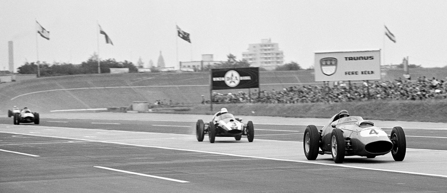 Tony Brooks, in the the Ferrari 246/F1, followed closely by the Cooper of Masten Gregory on the main straight