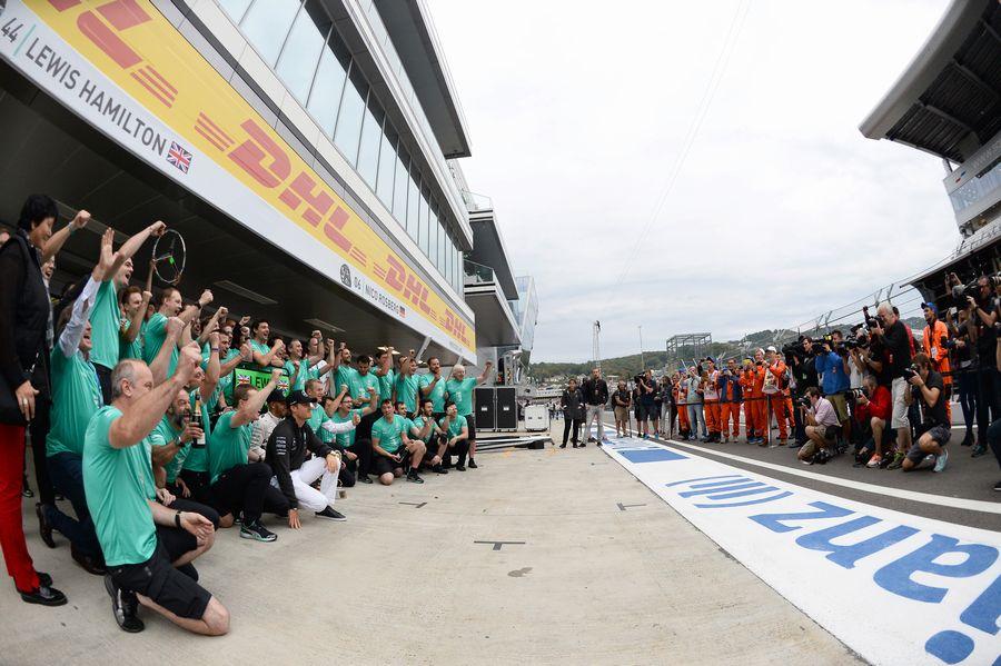Lewis Hamilton celebrates with Nico Rosberg and the team