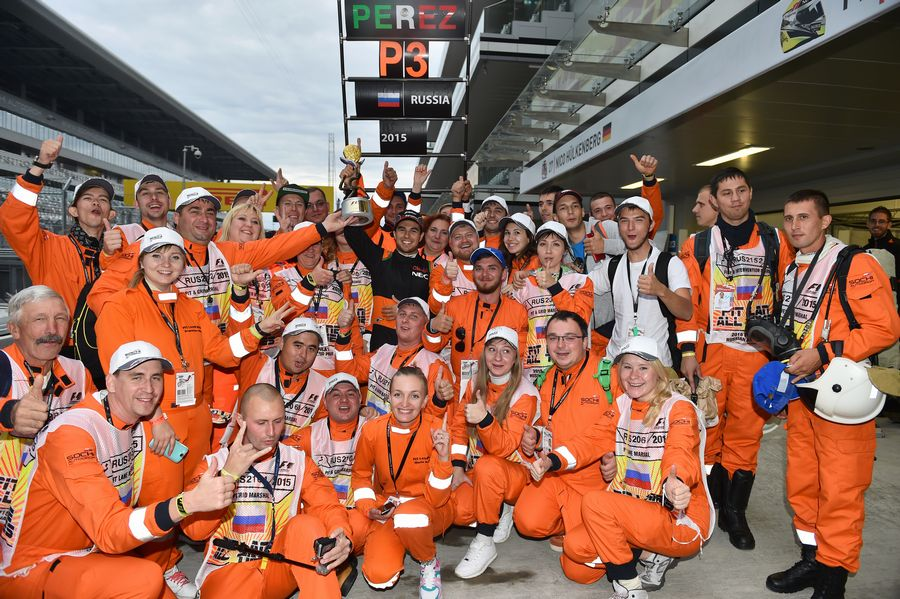 Sergio Perez celebrates third place with the marshals