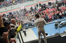 Lewis Hamilton shares some of champagne with fans