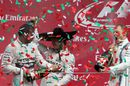 Top three drivers celebrate on the podium with champagne