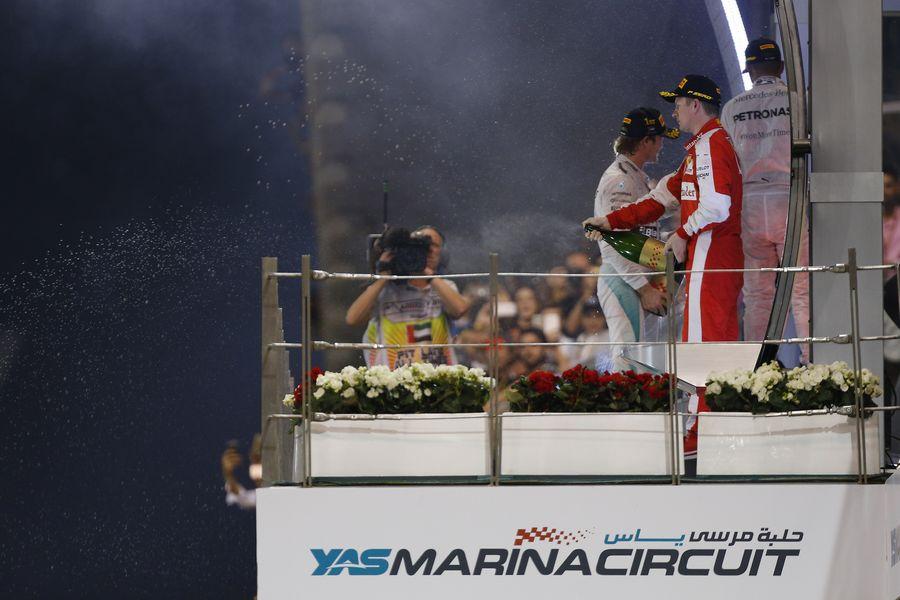 Kimi Raikkonen celebrates on the podium with champagne