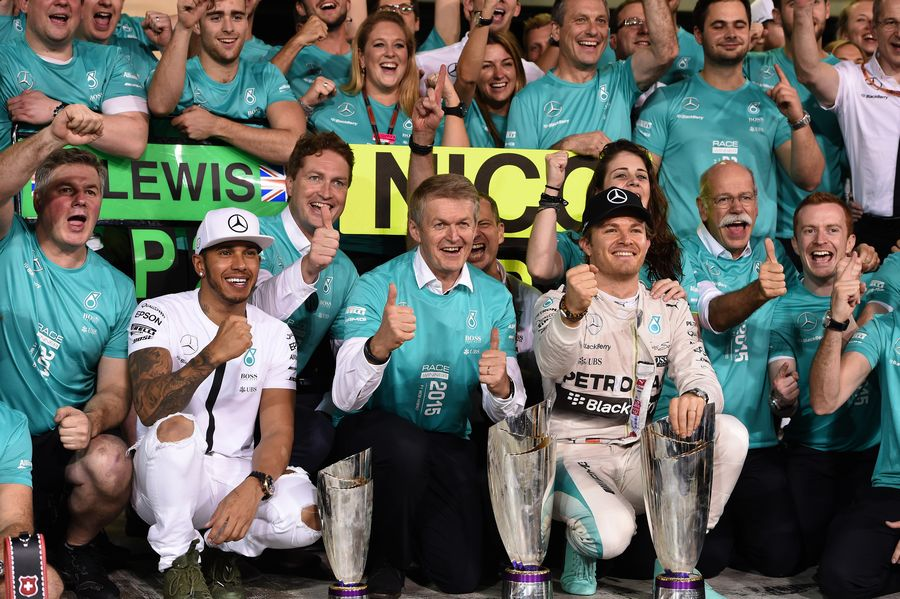 Nico Rosberg celebrates with Lewis Hamilton and Mercedes members